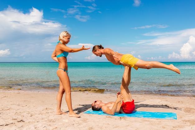 2つの若い男性と女性が一緒にフィットネスヨガ運動をしているビーチで。強さとバランスのアクロヨガ要素