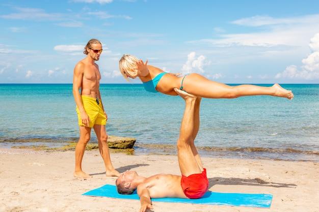 一緒にフィットネスヨガの練習をしているビーチで2人の若い男性と女性。強度とバランスのためのアクロヨガ要素。