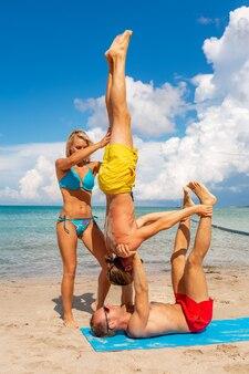 一緒にフィットネスヨガ運動をしているビーチで2人の若い男性と女性