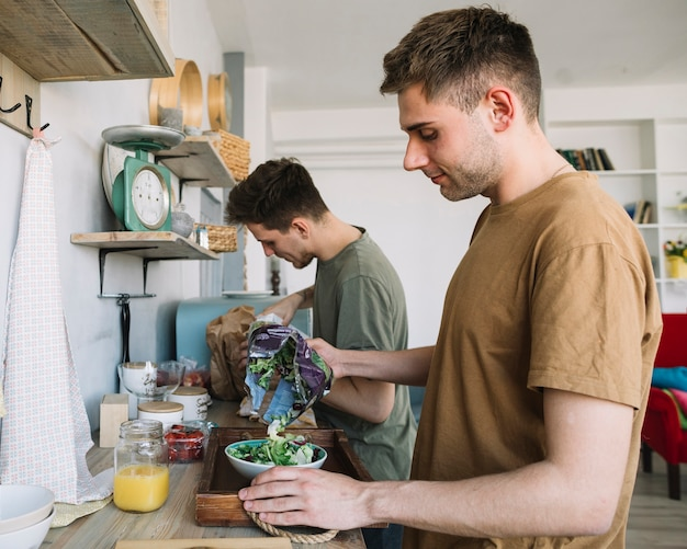 Two young man making morning breakfast in kitchen