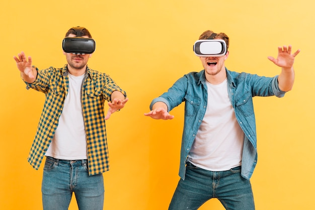 Two young man using virtual reality goggles touching in the air against yellow background