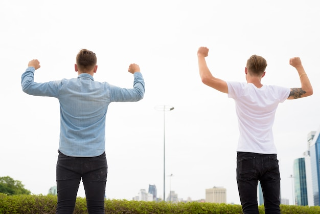 Two young man with arms raised outdoors