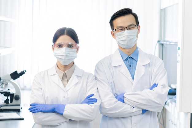 Two young masked intercultural scientists in whitecoats and gloves standing in front of camera while working over vaccine in laboratory