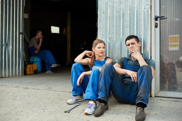Two young mechanics sitting near the entrance to car automotive service. male mechanic is smoking.