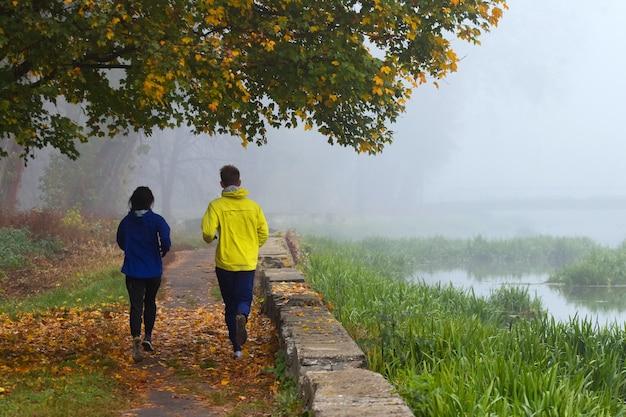 男と女の2人の青年が秋の公園で朝のランニングをする