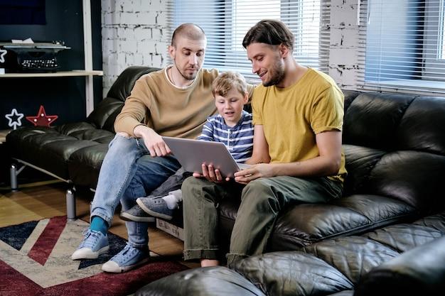 Двое молодых людей и маленький мальчик сидят на диване у себя дома и смотрят мультик или обучающее видео на ноутбуке