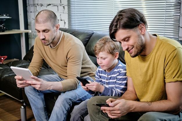Двое молодых людей и маленький мальчик с помощью мобильных гаджетов, сидя на диване у себя дома