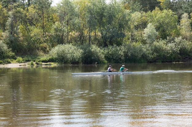 Two young men are sailing along the river in a kayak.