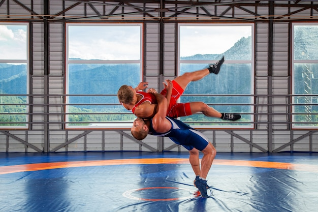 Two young men in blue and red wrestling tights are wrestlng and making a suplex wrestling