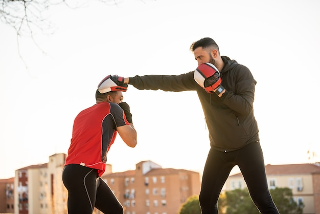 Two young men boxing outdoors