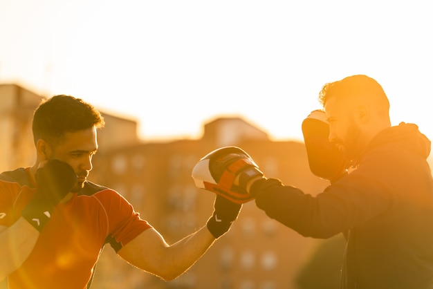 Two young men boxing outdoors.