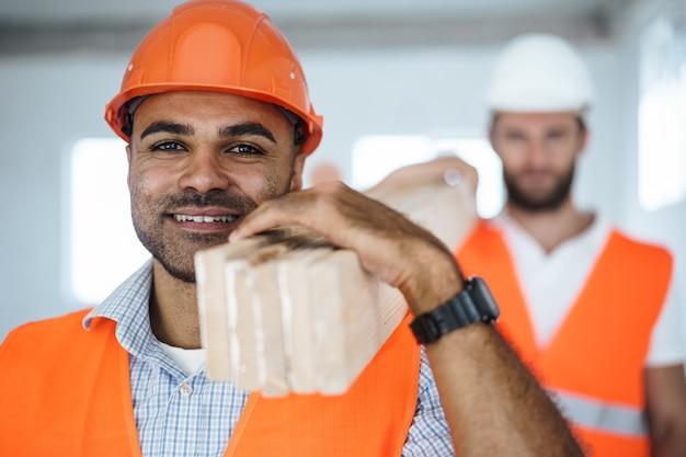 건설 현장에서 나무 판자를 들고 있는 두 젊은 남자 건축업자가 닫습니다.