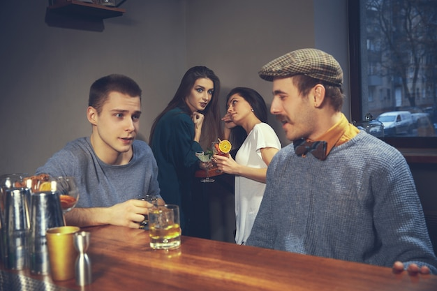Two young men in casual clothes talking while sitting at bar counter in pub