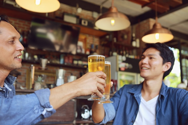 Two young men colliding with two glass of beer to celebrate their success.