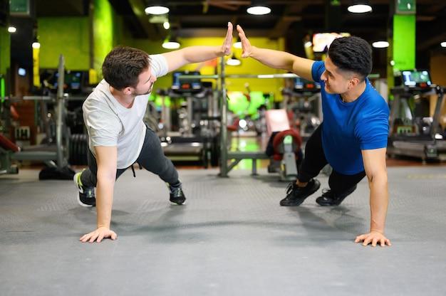 ジムで高い板をやっている2人の若い男性。