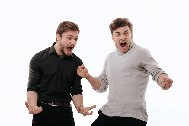 Two young men enjoying winning open their mouth, isolated white space, copy space, facial emotions positive