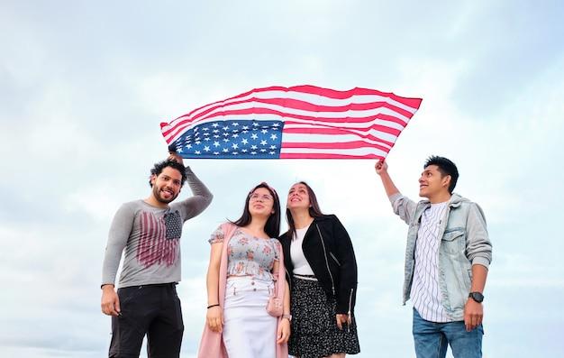 바람에 미국 국기를 들고 있는 두 젊은이와 깃발 아래 두 여성이 서 있습니다.