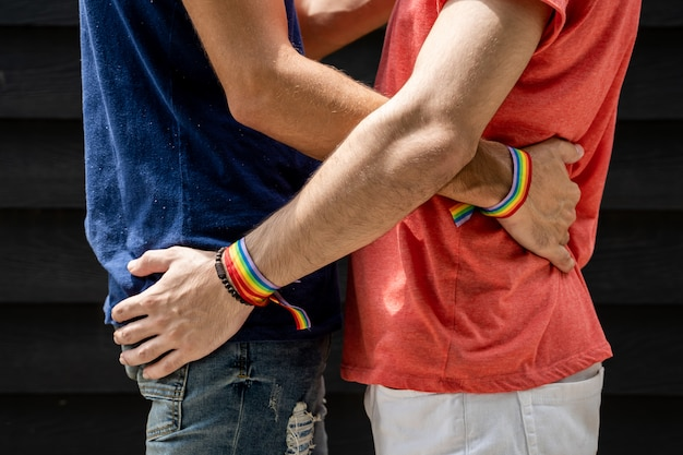 Two young men hugging each other at the waist with bracelets with the lgtb flag outside