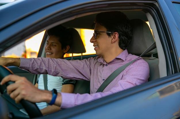 운전 세션에서 두 젊은이 강사가 젊은이에게 운전을 가르치고 있습니다.