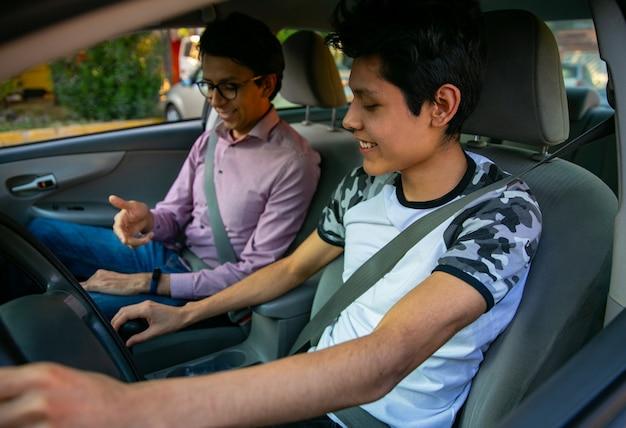 운전 세션에서 두 젊은이가 강사가 젊은이에게 운전을 가르치고 있습니다.