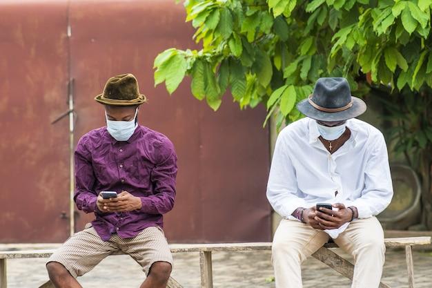 휴대전화를 사용하고 야외에 앉아 있는 보호용 안면 마스크를 쓴 두 젊은이