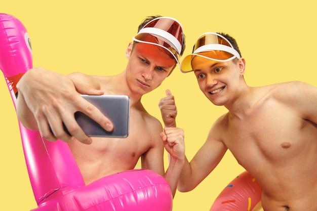 黄色のスタジオで分離された2つの若い男性