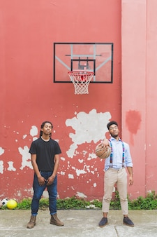 Two young men outdoor playing basket