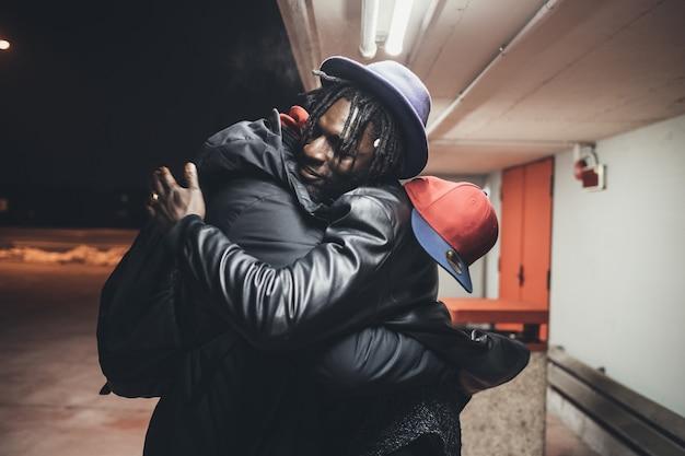Двое молодых людей на улице автостоянка приветствия обнимаются