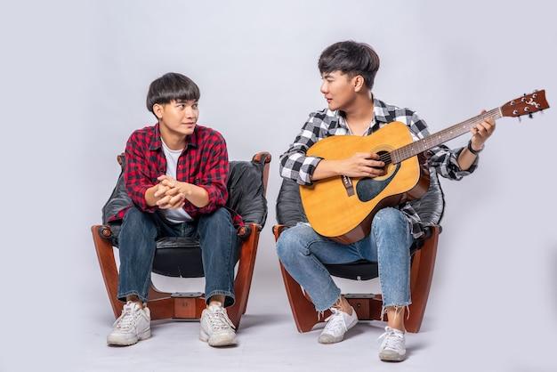 Due giovani uomini si sono seduti su una sedia e hanno suonato la chitarra.