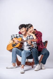 Two young men sat on a chair and played guitar.