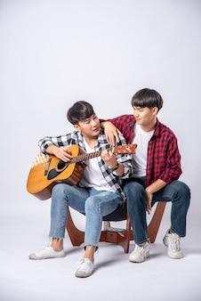 2人の若者が椅子に座ってギターを弾きました。