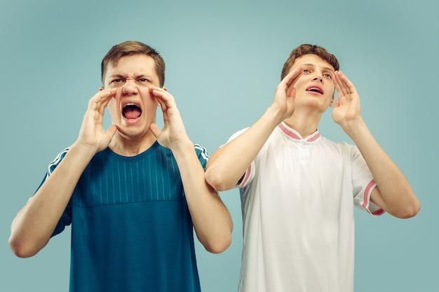 孤立したスポーツウェアに立っている2人の若い男性。スポーツ、サッカー、サッカーのクラブやチームのファン。友達の半身像。人間の感情、顔の表情の概念。