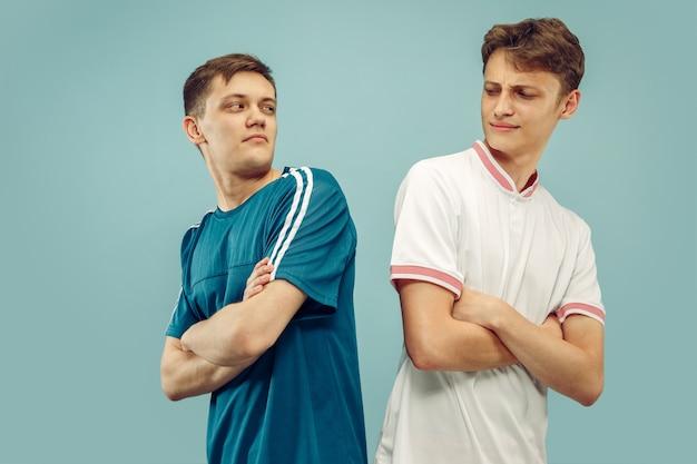 Два молодых человека, стоящие в изолированной спортивной одежде. поклонники спорта, футбола или футбольного клуба или команды. поясной портрет друзей. понятие о человеческих эмоциях, выражении лица.