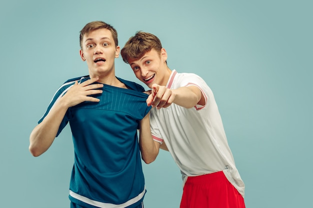青で隔離のスポーツウェアに立っている2人の若い男性