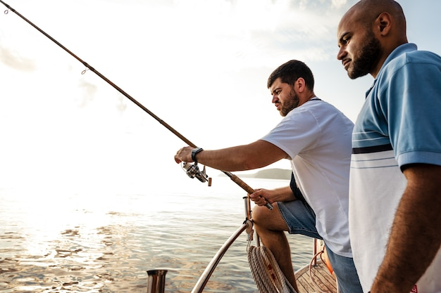 Two young men standing on sailboat with fishing rod looking at haul
