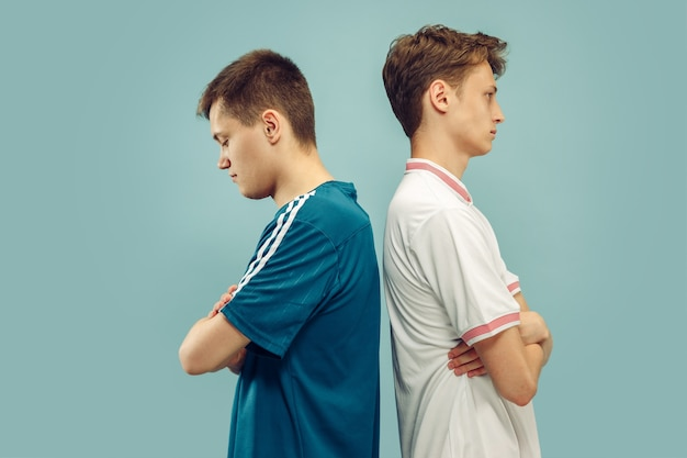Due giovani uomini in piedi in abbigliamento sportivo isolato sull'azzurro