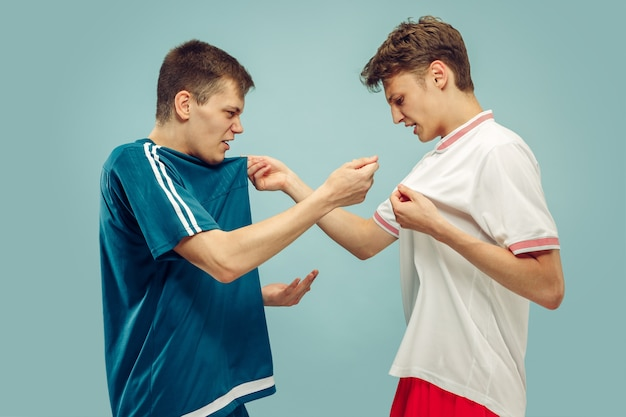 Two young men standing in sportwear isolated. fans of sport, football or soccer club or team. friends' half-length portrait. concept of human emotions, facial expression.