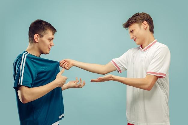 Due giovani uomini in piedi in abbigliamento sportivo isolato. appassionati di sport, calcio o club o squadra di calcio. ritratto a mezzo busto degli amici. concetto di emozioni umane, espressione facciale.