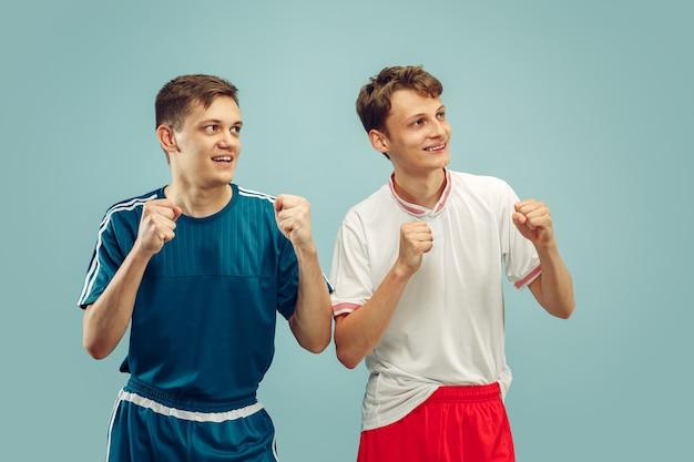 Due giovani uomini in piedi in abbigliamento sportivo isolato. i tifosi della squadra di sport. ritratto a mezzo busto di bellissimi modelli maschili. concetto di emozioni umane, espressione facciale. vista frontale.