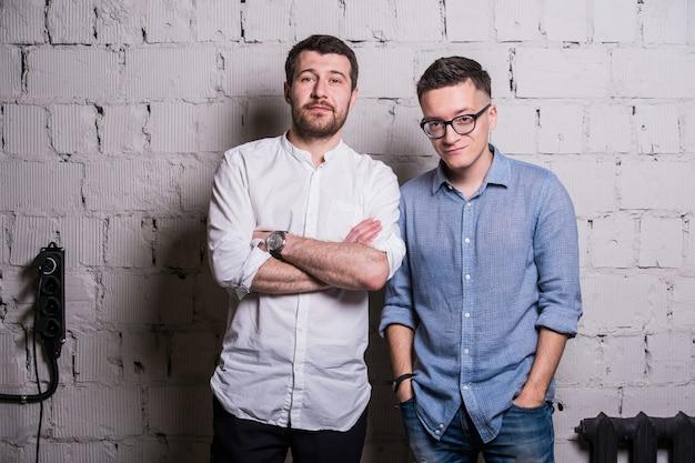 Два молодых человека стартаперов над серой кирпичной стеной лофт дизайн интерьера