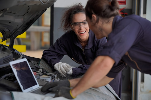 Two young men and women car mechanic i am using a laptop to check and condition the engine.
