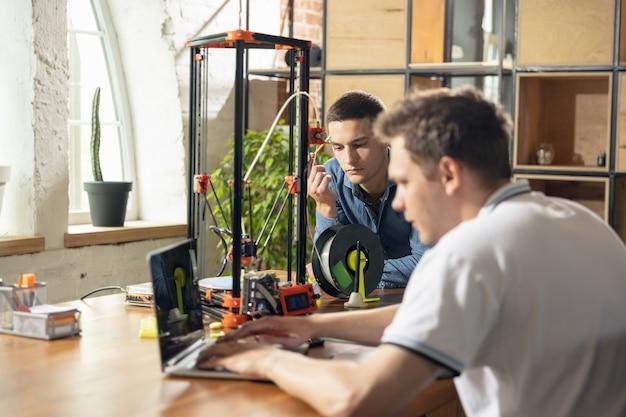 인쇄 장치로 집에서 일하는 두 젊은이
