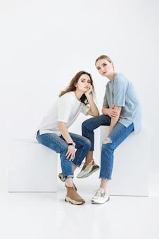 カジュアルな服を着てスタジオの白いシーンで立方体に座ってポーズをとる2人の若いモデル