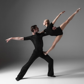 Two young modern ballet dancers on gray