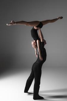 灰色のスタジオの背景に2人の若い現代バレエダンサー