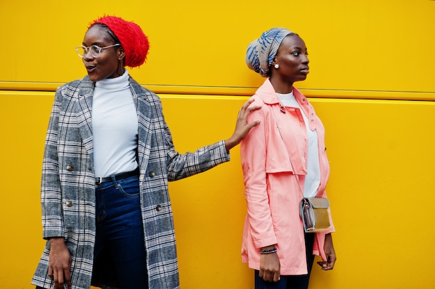 Two young modern fashionable, attractive, tall and slim women in hijab and coat posed against yellow bus
