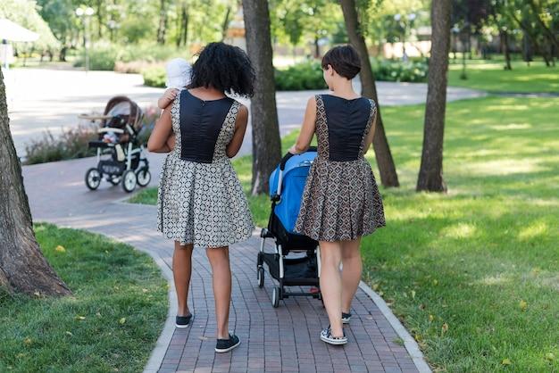 Две молодые матери толкают коляски в летнем парке.