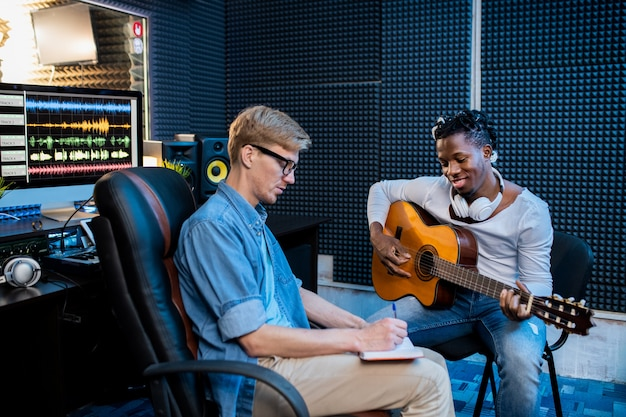Two young multicultural men playing guitar and making notes in notepad while making song in sound recording studio