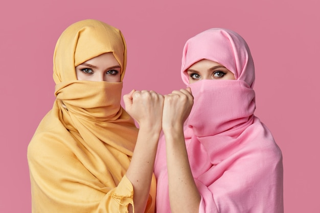 Two young muslim arabian women wearing colorful hijabs against pink wall Premium Photo