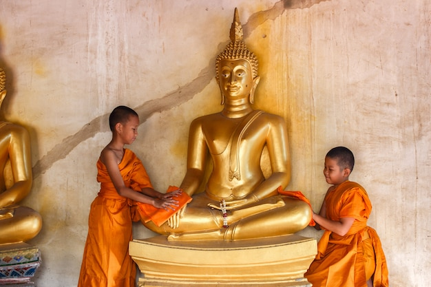 Two young novices monk scrubbing buddha statue at temple in thailand